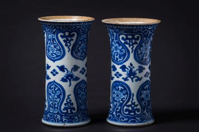 A pair of Chinese blue and white sleeve vases painted with lotus blooms between bold ruyi-head and floral borders, Kangxi, 17cm high, [some damage].