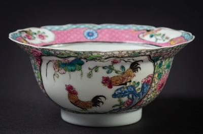 A Chinese porcelain famille rose cockerel bowl the finely potted circular bowl with notched rim, the exterior painted with two panels containing a pair of cockerels amongst flowering peony and pierced rock, flanked by chrysanthemum and reserved on a trellis ground, the interior with a single peony within a pink trellis and diaper border, Yongzheng, 15cm diameter, [tiny filled chip].