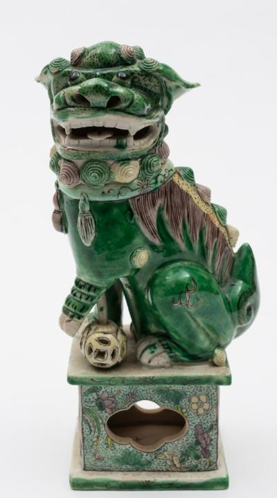 A Chinese famille verte biscuit Buddhist lion decorated in green, yellow and aubergine and modelled with open mouth, one front paw resting on a loose pierced brocade ball, on pierced rectangular stand, Kangxi, 23cm high.
