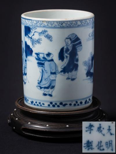 A Chinese blue and white cylindrical brushpot painted with three figures and a deer in a continuous landscape with pine trees and rockwork, apocryphal six-character Chenghua mark, 12.5cm high and wood stand.