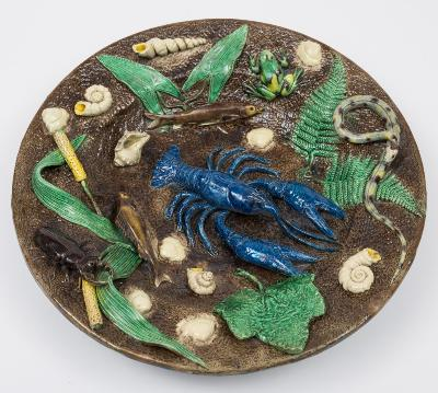Francois Maurice, a Paris School Palissy Ware dish of shallow circular form modelled with a lobster, snake, frog, two fish and scattered sea shells, the rim with a large stag beetle, fern, foliage and bull rush on a textured brown ground, the rim incised F Maurice, circa 1875-85, 40cm diameter, [minor chips to foot rim].