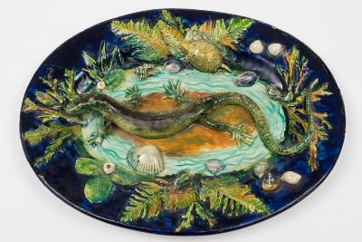 A French Palissy Ware dish of oval form, modelled with a lizard, small terrapin and frog amongst scattered shells and foliage, reserved on a blue ground, inscribed verso 'Boch 1892', 30cm long, [some over painting].