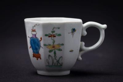 A fine early Worcester polychrome coffee cup of octagonal form with scroll handle, painted with an elegant Chinese lady, two flower vases, butterflies and flowering plants, scratch mark, circa 1753-5, 6cm high.