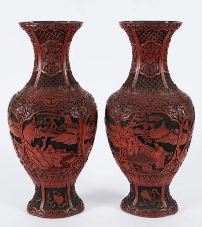 A pair of Chinese two-colour cinnabar lacquer carved vases of lobed baluster form with waisted neck and flared rim, with cartouche panels decorated with figures in mountainous landscapes, enclosed by trailing flowers and foliage, the ovoid spreading bases decorated with the emblems of the eight immortals, 43cm high.