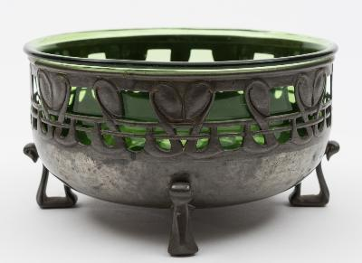 Archibald Knox design for Liberty & Co, a Tudric pewter and green glass bowl model No 0924, the sides with pierced stylised foliate border, with a green glass liner, probably by James Powell of Whitefriars, on four shaped feet, stamped marks, 17.4cm diameter.