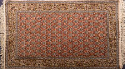 An Isfahan rug, the brick red field with a repeating design of urns of flowers and foliage and twin birds, enclosed by a main beige border with an all over design of flowers, foliage, urns and birds, having inscription to the fringed end, 242cm x 150cm.