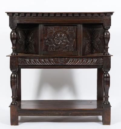 A 17th Century carved oak court cupboard, of small size, the top with a dentil edge, the canted central cupboard enclosed by a door decorated with a flowerhead rosette within gouged leaves and scrollwork, having similar panels to either side, the gadrooned drawer below with a central flowerhead, on turned column uprights, untied by an undertier, terminating in block feet, 114.5cm (3ft 9in) wide, 122cm (4ft) high.