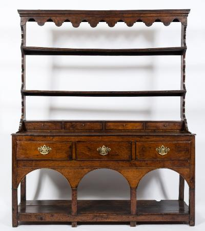 An 18th Century oak dresser, the shelved superstructure with a moulded cornice and arcaded frieze, having four small drawers below, the base containing three drawers in the arcaded apron, on square section uprights, united by an undertier, terminating in block feet, 150cm (4ft 11in) wide.