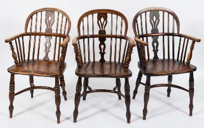 A harlequin set of four early 19th Century elm, ash and fruitwood stick back Windsor elbow chairs, the backs each with a pierced central splat, having shaped solid seats, on turned and tapered splayed legs, united by crinoline stretchers.