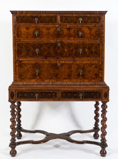An early 18th Century walnut oyster veneer crossbanded and inlaid chest on later stand, bordered with geometric sycamore lines, the upper part with a moulded cornice, containing two short and three long drawers, the stand containing two short drawers on later spirally turned legs headed with navette shaped medallions, united by undulating flattened X-frame stretchers, terminating in bun feet, 107cm (3ft 6in) wide, 154.5cm (5ft 0 3/4in) high.