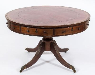 A Regency mahogany and inlaid circular drum top library table, bordered with ebony lines, the top inset with a panel of tooled leather, containing alternate frieze and dummy drawers and with a hinged fitted pen drawer, on turned central column and reeded quadruped splayed legs, terminating in brass cappings and castors, 121cm (3ft 11 1/2in) diameter.