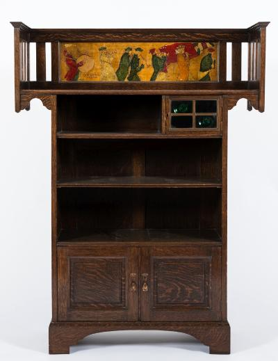 By Shapland and Petter, Barnstaple An Edwardian oak and decorated bookcase, the overhanging railed top with a moulded and painted panel of processional figures titled 'The Village Band', having a small enclosed glazed bullseye compartment and open shelves below with cupboard at base enclosed by a pair of moulded fielded panel door, on bracket feet, 110cm (3ft 7 1/4in) wide, 143cm (4ft 8 1/4in) high, the lock stamped S & PB.