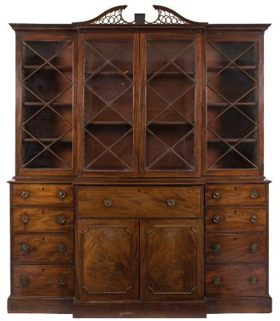 A George III mahogany breakfront secretaire library bookcase, with pierced fret, the upper part with a pierced fret central swan neck pediment, enclosed by a pair of central astragal glazed panel doors, flanked by an enclosed astragal glazed cupboard to either side, the lower part having a central fall enclosing a fitted interior with small drawers and pigeon holes, the cupboard below enclosed by a pair of doors flanked by four short drawers to either side, on a plinth base, 201cm (6ft 7in) high, 235cm (7ft 8 1/2in) high.