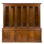 Sale FS30; Lot: 0881: An early Victorian oak library bookcase, of large size, the upper part with a moulded cornice, fitted with adjustable shelves enclosed by three pairs of pointed arch lozenge wire mesh panel doors between fluted pilasters carved with rosettes, the lower part with a moulded edge fitted with three short panelled frieze drawers and enclosed by three pairs of recessed pointed arch panelled doors below, between similar pilasters, on a plinth base, 284cm (9ft 4in) long, 272cm (8ft 11in) high.