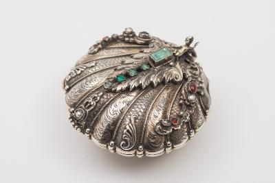 A 19th century Continental silver ring casket of shell-shaped outline, the hinged lid inset with emeralds, garnets and seed pearls and surmounted by a putto, having applied foliate and scroll decoration, with a gilded interior and raised on a circular palmette decorated foot, 8cm wide, 5.62ozs.