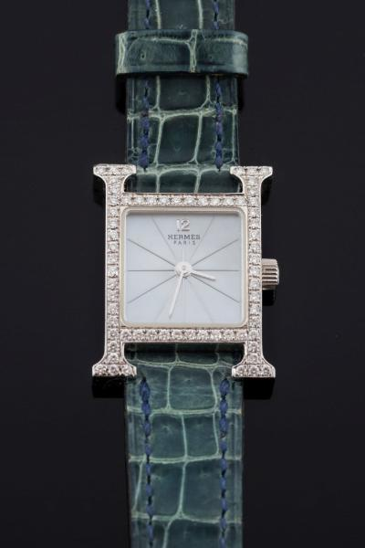 Hermes. A lady's 18ct white gold and diamond-set 'H' wristwatch the signed mother of pearl dial with radiating markers in an 'H'-shaped case 25mm long x 17.5mm wide, set with brilliant-cut diamonds, the reverse with 'Hermes' insignia and inscribed 'HH1.191 2093760' with convention marks and Swiss control mark on a grey/blue strap in wallet.