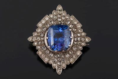 Sale FS30; Lot: 0177: A sapphire and diamond lozenge-shaped brooch with central cushion-shaped sapphire 10.1mm long x 8.8mm wide x 7.4mm deep, estimated to weigh 5.0ct, claw-set within a surround of rose and eight-cut diamonds, 6gms gross weight.