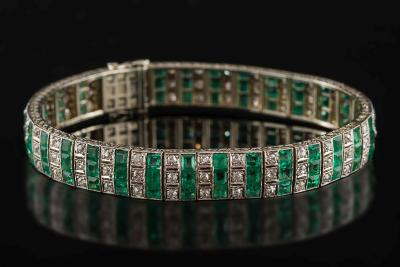 An art deco platinum-faced gold, emerald and diamond bracelet, with rectangular emeralds and round old brilliant-cut diamonds set in rows of three, the clasp stamped '18ct Pt', approximately 19.5cm total length, 29gms gross weight.
