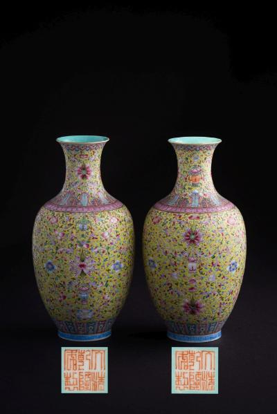 A pair of Chinese eggshell porcelain lime-green ground vases each of ovoid form with waisted neck and everted rim, finely painted with lotus blooms and leafy strapwork and other flowers, reserved on a lime-green ground between lappet and diaper borders, turquoise glazed interior and base, apocryphal iron-red Qianlong six-character seal marks, early 20th century, 19cm high with carved hardwood stands and in fitted case.
