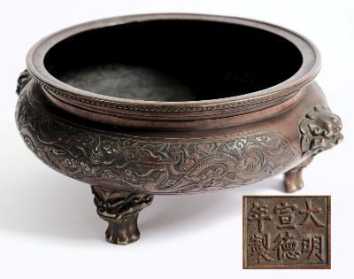 Sale FS30; Lot: 0615: A Chinese bronze tripod censer with banded decoration of dragons chasing pearls, with dragon mask handles to the side, raised on three dragon mask feet, bears six character mark, 22cm diameter.