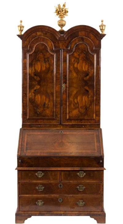 An early 18th Century walnut double dome bureau cabinet, the upper part surmounted by later giltwood urn finials centred by a floral foliate urn, the interior with pigeon holes enclosed by a pair of later domed arch moulded panel doors, the cross and feather banded waisted lower part with a quarter veneered sloping hinged fall enclosing a shaped interior with concave fronted pigeon holes and well with sliding cover, containing two short and two long drawers below, on bracket feet, 97cm (3ft 2in) wide (with renewals).