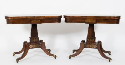 A pair of Regency rosewood and brass inlaid rectangular card tables, bordered with lines and decorated with foliate scroll designs and paterae, the baize lined hinged tops with rounded corners, the friezes each with a central foliate scroll cut marquetry panel on tapered rectangular beaded columns, platforms and quadruped splayed legs, terminating in brass lions claw cappings and castors, 92cm (3ft 0 1/4in) wide (one re-polished).