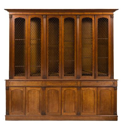 An early Victorian oak library bookcase, of large size, the upper part with a moulded cornice, fitted with adjustable shelves enclosed by three pairs of pointed arch lozenge wire mesh panel doors between fluted pilasters carved with rosettes, the lower part with a moulded edge fitted with three short panelled frieze drawers and enclosed by three pairs of recessed pointed arch panelled doors below, between similar pilasters, on a plinth base, 284cm (9ft 4in) long, 272cm (8ft 11in) high.