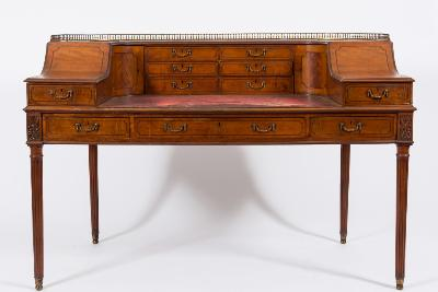 By John Watson, 8 New Oxford St WC - A late 19th Century satinwood and inlaid Carlton House writing desk, bordered with ebony and boxwood lines, the curved superstructure with a brass baluster gallery rail, fitted with six small drawers, flanked by a pair of compartments with brass posting apertures, each enclosed by a curved door, the curved fronts each fitted with a small drawer and with tooled crimson leather inset writing surface, the frieze containing three short drawers, flanked by carved paterae, on turned and fluted tapered legs, terminating in brass sabots, 157cm (5ft 2in) wide, the centre frieze drawer stamped John Watson, 8 New Oxford St, W C.
