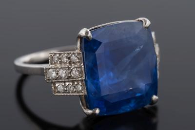 A platinum, sapphire and diamond ring with central cushion shaped sapphire, 14.7mm x 13.5mm x 8.7mm deep between three-row diamond-set shoulders, ring size N 1/2, 9.8gms gross weight.
