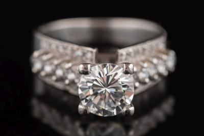 A diamond single-stone ring the circular, brilliant-cut diamond approximately 7.2mm diameter, estimated to weigh approximately 1.5cts in a raised four-claw setting between diamond-set shoulders, the shank stamped '18K', ring size 'M'.