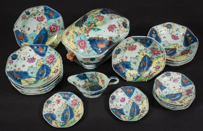 A Chinese Export 'Tobacco Leaf' part dinner service of octagonal form, decorated in bright famille rose colours, underglaze blue and gilt with large overlapping leaves, blossom and hibiscus, Qianlong, comprising: a tureen and cover with Buddhist lion head handles and large fruiting pomegranate finial, a sauceboat, ten plates, 22cm, seven deep plates, 22cm, eight small plates, 16cm [damages].