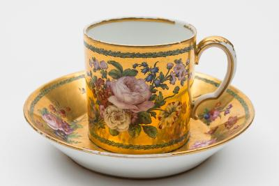 Sale FS31; Lot: 0686: A Sevres hard-paste porcelain coffee can and saucer with scroll handle, finely painted with bouquets and floral sprays within laurel leaf borders on a gilt ground, puce interlaced LLs mark with date letters GG for 1784 and artist's mark in the form of a leafy branch probably for Nicolas Schradre, diameter of saucer 15cm [some rubbing to gilt on rims, minor stacking ware].