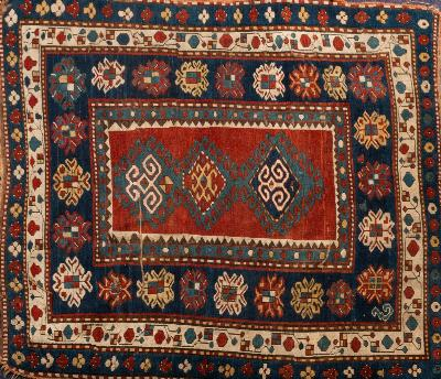 A Kazak rug, the red oblong central panel with triple hooked geometric medallions, enclosed by indigo and ivory triple border with geometric designs, 147cm x 133cm.