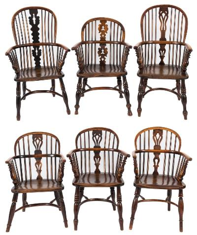 Six early 19th Century stick back Windsor elbow chairs, five being in yew wood, elm and beech, one in elm, ash and beech; the arched backs each with a pierced central splat and shaped solid seat, on turned and tapered splayed legs with crinoline stretchers.