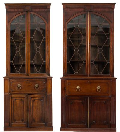 Two matching early 19th Century mahogany secretaire bookcases, the upper parts each with a later moulded cornice and a reeded and panelled frieze, fitted with adjustable shelves enclosed by a pair of domed astragal glazed lozenge and roundel panel doors, the lower parts each with a hinged fall; one enclosing a contemporary fitted interior with small drawers and pigeon holes, the cupboards below enclosed by pairs of cockbeaded panel doors, between reeded stiles, on plinth bases (one 110.5cm (3ft 7 1/2in) wide, 250.5cm (8ft 2 3/4in) high, the other 97.5cm (3ft 2 1/2in) wide, 251.5cm (8ft 3in) high).