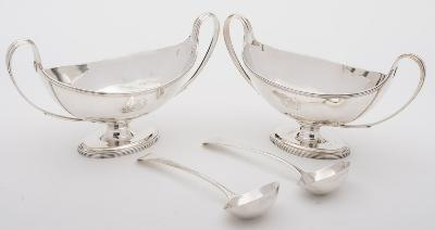 A pair of George III silver sauce tureens, maker Henry Chawner, London, 1787 crested, of boat-shaped outline, with reeded swept handles, raised on oval spreading feet, 25cm wide, together with a pair of George III silver Old English pattern sauce ladles, maker Thomas Northcote & George Bourne, London, 1794, total weight of silver 28.18ozs.