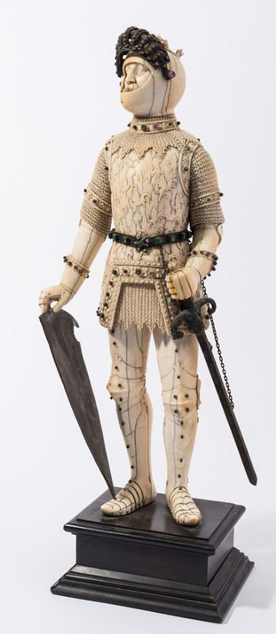A large late 19th century German carved ivory, metal and paste mounted figure of a medieval knight in full chain mail and armour applied with 'jewels' and holding a sword and shield, the figure 43cm high [some damage and age cracks] on ebony mounted stand.