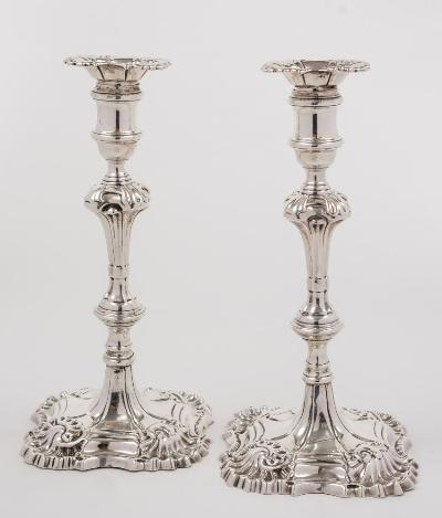Sale FS34; Lot: 0190: A pair of George III cast silver candlesticks, maker William Cripps, London, 1769 with unmarked foliate decorated drip trays, having urn -shaped nozzles on a knopped and tapering stem raised on a square foliate and stepped base, 25cm high, 40.59ozs.