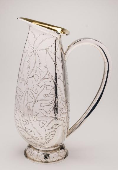 An Elizabeth II silver jug, maker Rod Kelly, London, 2007 of triangular ovoid form with gilded interior and chased foliate decoration to the exterior, on a domed and spreading circular base, 29.5cm high, 42.10ozs.