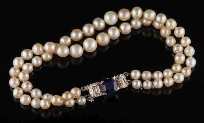 Sale FS34; Lot: 0261: A graduated pearl/cultured pearl two-string bracelet with sapphire and diamond mounted clasp:, the strings each with 31 pearls graduated from 5mm to 7mm diameter secured to a rectangular sapphire and diamond mounted clasp. Please note, pearls un-tested.