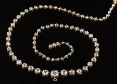 Sale FS34; Lot: 0348: A late 19th century graduated diamond riviere necklace with circular, old-cut diamonds in cut down collet settings, the central diamond approximately 6.7mm diameter x 3.7mm deep and estimated to weigh 1.0cts, on diamond three-stone clasp, total diamond weight approximately 11.0cts, 43cm total length, 20gms gross weight.