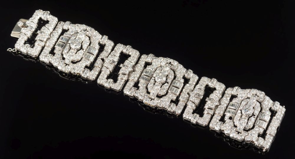Sale FS35; Lot: 0360: A 1930s diamond mounted bracelet with three large rectangular openwork links and three smaller links pave and channel-set with brilliant and baguette-cut diamonds (two settings vacant) estimated to weigh a total of 35cts including three principal circular diamonds each approximately 1.25cts, 104gms gross weight and in fitted case.