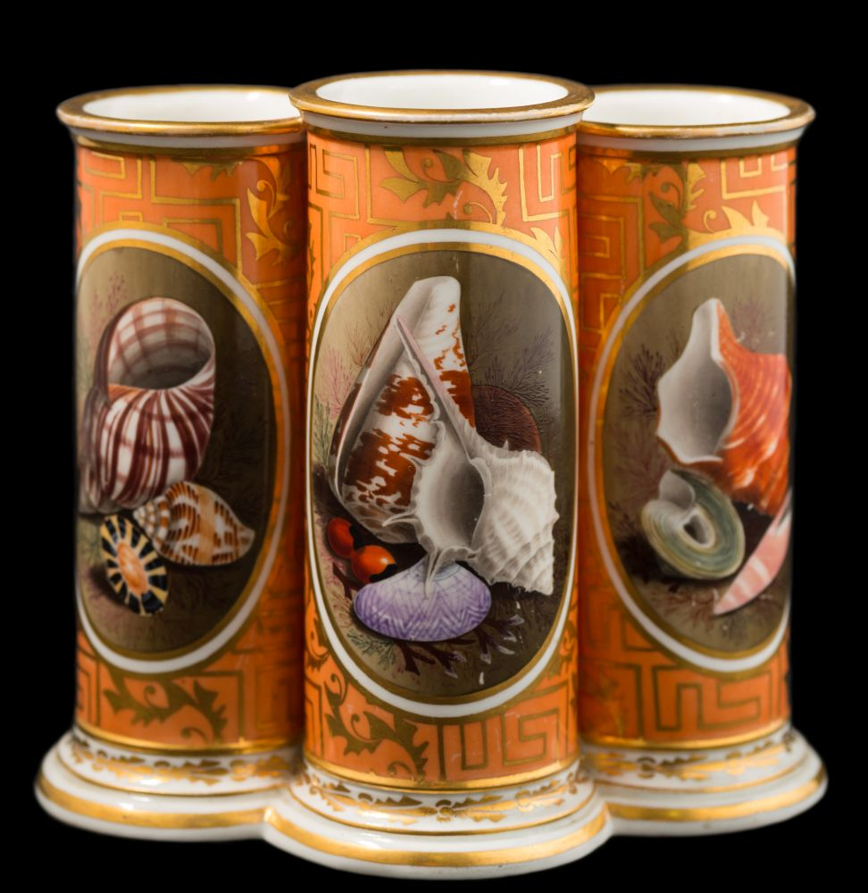 Sale FS35; Lot: 0771: A Barr [Worcester] triple spill vase the three conjoined cylindrical vases finely painted with oval panels of seashells and seaweed on a fret and foliate gilded orange ground, incised B mark, circa 1800-05, 14.5cm high [minor wear to gilding on rims].