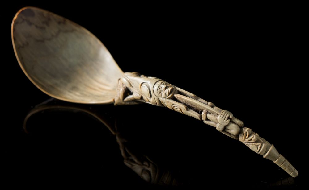 Sale FS35; Lot: 0875: A Northwest Coast Native American carved horn spoon with pear-shaped bowl, the carved handle depicting a figure being eaten by a giant fish, the terminal in the form of a seated deity, 25cm long.