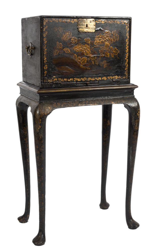Sale FS35; Lot: 1103: An 18th Century Anglo-Indian and chinoiserie decorated cabinet on stand, with peony and chrysanthemum blossom and foliage heightened in gilt on a black lacquer ground, the cabinet with a hinged fall enclosing an ivory inlaid interior with stellar, foliate and lozenge geometric designs, containing an arrangement of six drawers, having a candle slide below and brass drop carrying handles to the sides, the stand on cabriole legs, terminating in pad feet, the cabinet 44.5cm (1ft 5 1/2in) wide, the stand 53cm (1ft 9in) wide, overall height 103.5cm (3ft 4 3/4in), with restorations.