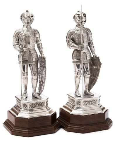 A pair of German silver figures of knights in armour, bears import marks for Adolph Barsach Davis, London, 1928 each wearing full armour with griffin and scroll decoration, hinged visors, shaped shields, one holding a partisan, the other holding a double headed axe, mounted on square bases with canted corners, raised on polished wood plinths, total height 28cm high, total weight of silver 27.22 ozs.