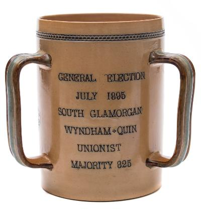 A Doulton Lambeth 'South Glamorgan Election' stoneware tyg inscribed 'General Election July 1895 South Glamorgan Wyndam:Quin Unionist Majority 825', impressed marks and numbered 4920, retailed by Mortlocks Ltd., London, 17cm high.