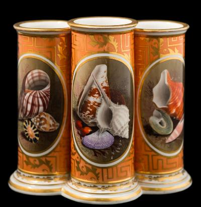 A Barr [Worcester] triple spill vase the three conjoined cylindrical vases finely painted with oval panels of seashells and seaweed on a fret and foliate gilded orange ground, incised B mark, circa 1800-05, 14.5cm high [minor wear to gilding on rims].