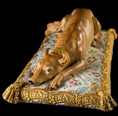 Sale FS35; Lot: 0788: A large Meissen porcelain group of Catherine II of Russia's favourite dog modelled after the original by Johann Joachim Kaendler, wearing a gold collar and lying on a brocade edged rectangular cushion with tassels, blue crossed swords mark and rubbed inscription that should read 'Chien favorit de feu SM l'Imperatrice Catherine de Russie', circa 1850-70, 43cm long, [small losses to tassels].