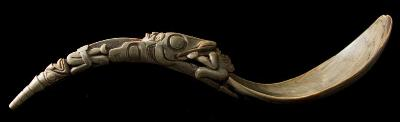 A Northwest Coast Native American carved horn spoon with pear-shaped bowl, the carved handle depicting a figure being eaten by a giant fish, the terminal in the form of a seated deity, 25cm long.
